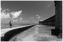 Park visitor looking, Fort Jefferson moat and seawall. Dry Tortugas National Park, Florida, USA. (black and white)