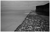 Brick seawall at dusk during a storm. Dry Tortugas National Park, Florida, USA. (black and white)