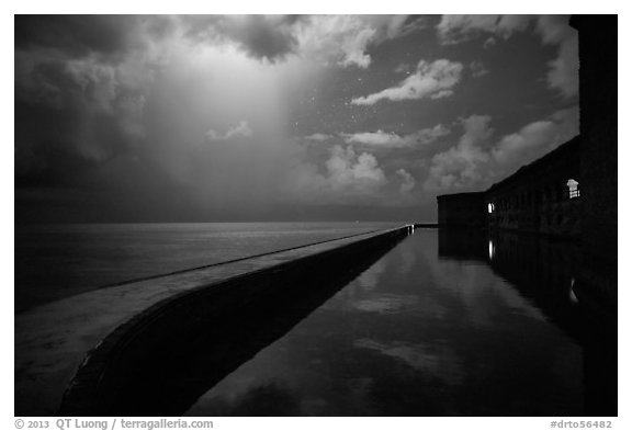 Fort Jefferson seawall at night with sky lit by tropical storm. Dry Tortugas National Park (black and white)