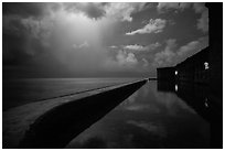 Fort Jefferson seawall at night with sky lit by tropical storm. Dry Tortugas National Park, Florida, USA. (black and white)