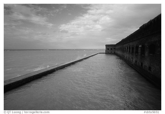 Seascape with fort seawall and moat on cloudy day. Dry Tortugas National Park (black and white)
