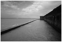 Seascape with fort seawall and moat on cloudy day. Dry Tortugas National Park, Florida, USA. (black and white)