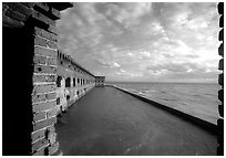 Fort Jefferson wall and moat, framed by cannon window. Dry Tortugas National Park, Florida, USA. (black and white)