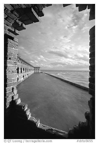 Fort Jefferson seawall and moat, framed by a crumpling embrasures, late afternoon. Dry Tortugas National Park (black and white)