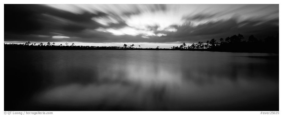 Dark clouds in motion at sunset over lake. Everglades National Park (black and white)