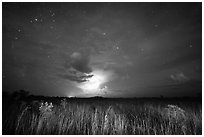 Sawgrass prairie with cloud lit by lightening. Everglades National Park, Florida, USA. (black and white)