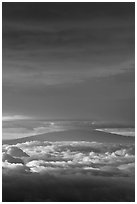 Mauna Kea above and below clouds, sunrise. Haleakala National Park, Hawaii, USA. (black and white)