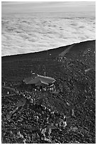 People gather to watch sunrise above sea of clouds. Haleakala National Park ( black and white)