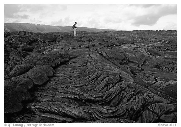Hiker on hardened lava flow at the end of Chain of Craters road. Hawaii Volcanoes National Park (black and white)