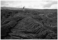Hiker on hardened lava flow at the end of Chain of Craters road. Hawaii Volcanoes National Park, Hawaii, USA. (black and white)
