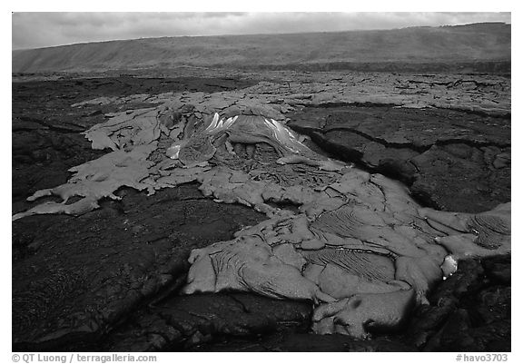 Live hot lava flows over hardened lava. Hawaii Volcanoes National Park (black and white)