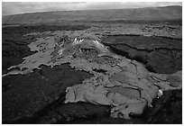 Live hot lava flows over hardened lava. Hawaii Volcanoes National Park, Hawaii, USA. (black and white)