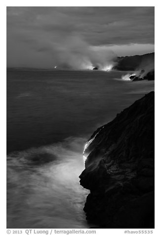 Molten lava pouring over sea cliffs at dawn. Hawaii Volcanoes National Park (black and white)