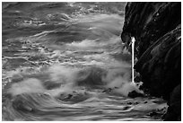Waves and lava spigot. Hawaii Volcanoes National Park, Hawaii, USA. (black and white)