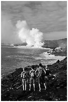 Hikers looking at molten lava and coastal volcanic steam cloud. Hawaii Volcanoes National Park, Hawaii, USA. (black and white)