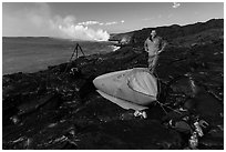 Photographer camping near lava ocean entry. Hawaii Volcanoes National Park, Hawaii, USA. (black and white)