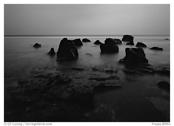 Rocks in water at dusk, Siu Point, Tau Island. National Park of American Samoa (black and white)