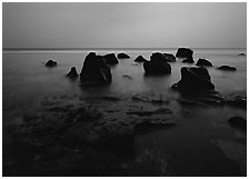 Rocks in water at dusk, Siu Point, Tau Island. National Park of American Samoa ( black and white)