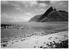 Tropical beach with sand and pebbles, and pointed peaks of Ofu Island. National Park of American Samoa (black and white)