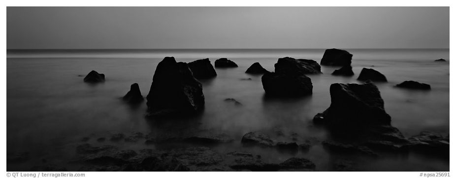 Seascape with boulders in water at dusk. National Park of American Samoa (black and white)