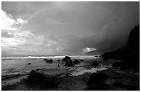 Boulders and coastline at sunrise with rainbow, Siu Point, Tau Island. National Park of American Samoa (black and white)