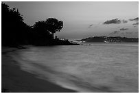 Honeymoon beach at dusk with lights of St Thomas. Virgin Islands National Park ( black and white)