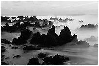 Volcanic rocks and waves at sunrise, Keanae Peninsula. Maui, Hawaii, USA (black and white)