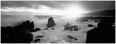 Primeval seascape with surf and rising sun. Maui, Hawaii, USA (Panoramic black and white)