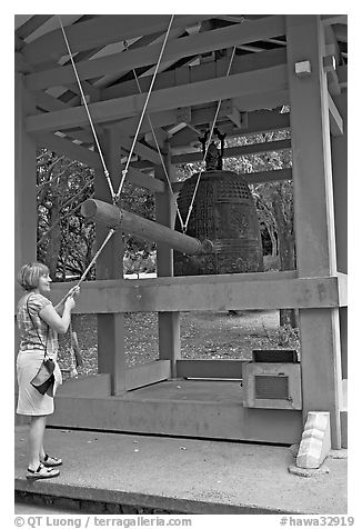 Tourist rings the sacred bell before entering Byodo-In temple. Oahu island, Hawaii, USA (black and white)