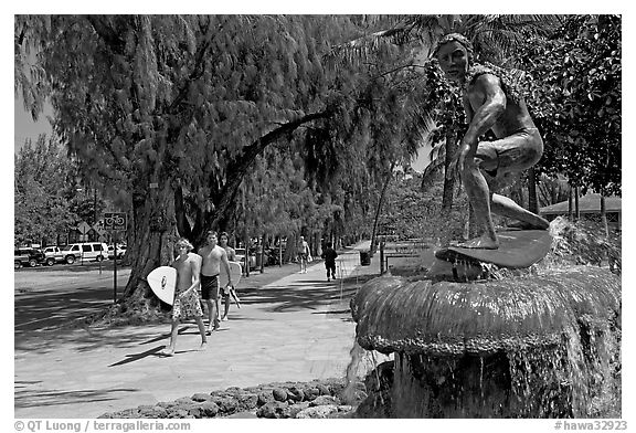 Young men carring surfboards next to statue of surfer, Kapiolani Park. Waikiki, Honolulu, Oahu island, Hawaii, USA (black and white)