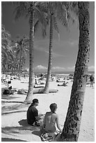 Couple under palm trees on Waikiki beach. Waikiki, Honolulu, Oahu island, Hawaii, USA (black and white)