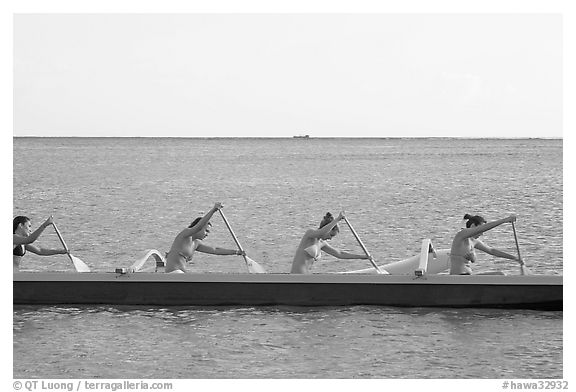 Side view of women in bikini paddling a outrigger canoe, Maunalua Bay, late afternoon. Oahu island, Hawaii, USA (black and white)