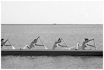Side view of women in bikini paddling a outrigger canoe, Maunalua Bay, late afternoon. Oahu island, Hawaii, USA ( black and white)