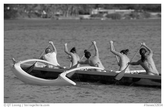 Back view of women in bikini paddling a outrigger canoe, Maunalua Bay, late afternoon. Oahu island, Hawaii, USA (black and white)