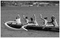 Back view of women in bikini paddling a outrigger canoe, Maunalua Bay, late afternoon. Oahu island, Hawaii, USA ( black and white)