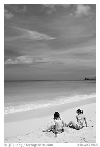 Young women sitting on Waimanalo Beach. Oahu island, Hawaii, USA (black and white)