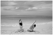 Young women stretching on Waimanalo Beach. Oahu island, Hawaii, USA (black and white)