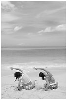 Young women doing gymnastics on Waimanalo Beach. Oahu island, Hawaii, USA (black and white)