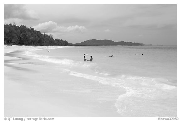 Couple and other bathers in the water, Waimanalo Beach. Oahu island, Hawaii, USA (black and white)
