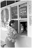 Woman with a flower in her hair getting shave ice, Waimanalo. Oahu island, Hawaii, USA (black and white)