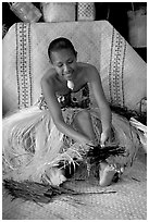 Fiji woman using her feet to tie leaves. Polynesian Cultural Center, Oahu island, Hawaii, USA ( black and white)