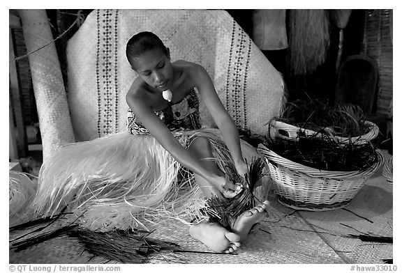 Fiji woman tying together leaves with her feet. Polynesian Cultural Center, Oahu island, Hawaii, USA (black and white)