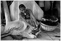 Fiji woman tying together leaves with her feet. Polynesian Cultural Center, Oahu island, Hawaii, USA ( black and white)