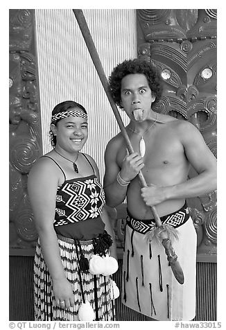 Maori woman and man sticking out his tongue. Polynesian Cultural Center, Oahu island, Hawaii, USA (black and white)