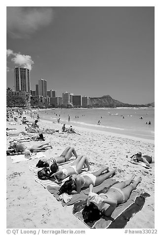 Young women on Waikiki Beach with skyline in the background. Waikiki, Honolulu, Oahu island, Hawaii, USA (black and white)