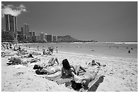 Young women sunning on Waikiki Beach. Waikiki, Honolulu, Oahu island, Hawaii, USA (black and white)