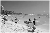 Men walking on Waikiki Beach with surfboards. Waikiki, Honolulu, Oahu island, Hawaii, USA (black and white)
