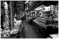 Woman and stands, International Marketplace. Waikiki, Honolulu, Oahu island, Hawaii, USA (black and white)