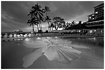 Swimming pool at sunset, Halekulani hotel. Waikiki, Honolulu, Oahu island, Hawaii, USA (black and white)