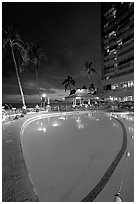 Swimming pool at night, with dance performance, Sheraton hotel. Waikiki, Honolulu, Oahu island, Hawaii, USA (black and white)